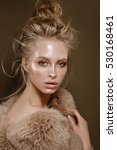 Small photo of Beautiful fashion portrait of a girl with glossy, glowing and radiant skin, a long neck, cusioning noobies , disheveled natural hair, in fur, on a neutral background, and the savage