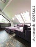 Small photo of Purple corner sofa and pouffe in an illuminated attic lounge room