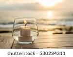 Candle On A Table At Sunset...