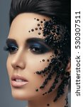 Small photo of Portrait of a beautiful brunette with makeup beauty and adornment on the face in the form of black stones