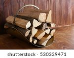 Basket With Firewood On Wooden...