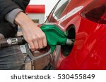 man is pumping gas in red car... | Shutterstock . vector #530455849