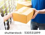 Small photo of Delivery man in blue uniform handing parcel box to recipient - courier service concept