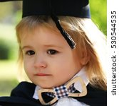 Small photo of Little boy child in black academic gown and squared school hat and bow tie with blonde hair standing outdoor on green natural background