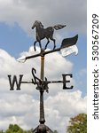Small photo of Horse weather vane against a blustery blue sky with clouds. Vertical.