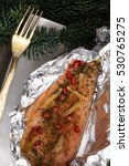 Small photo of Christmas recipe: salmon trout with ginger and pomegranate berries in aluminium foil