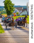 Small photo of Strasburg, PA - June 19, 2016: Multiple Amish buggies and wagons in summer on a county road in Lancaster County, PA.