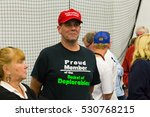 Small photo of Manheim, PA - October 1, 2016: A man wears a Proud Member of the Basket of Deplorables shirts and a Make America Great Again hat at a Donald Trump campaign rally.