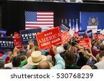 Small photo of Manheim, PA - October 1, 2016: People enthusiastically wave Make America Great Again Signs at a Donald Trump campaign rally.