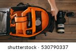 Photographe pack his camera and lenses to bagpack. Bag  appliances for photography top view.
