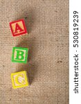 Small photo of wooden ABC blocks on sack background,Top view.