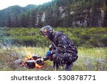Small photo of Man in camouflage preparing food on campfire in a clearing near the mountains. the Stalker, survive in the woods