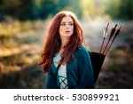 Close up portrait of  a beautiful red haired girl in green  medieval dress with bow and arrows. Fairy tale story about brave heart woman .Glowing sun on archer.Warm art work.Amazing model looking afar