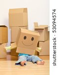 Little girl having fun in her new home unpacking playing with cardboard boxes - stock photo
