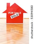 Selling houses concept with a sold sign on the floor indoors - stock photo