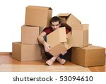 Man overrun by the issues of moving - covered with cardboard boxes - stock photo