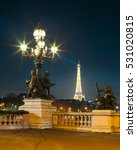 Small photo of PARIS, FRANCE - DECEMBER 5, 2016: View of the illuminated Eiffel Tower from the Alexander III Bridge at dusk. It's a deck arch bridge, regarded as the most ornate, extravagant bridge in the city.
