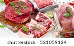 Small photo of Different types of raw meat with fresh herbs.