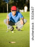 male golfer in a putting green analyzing his shot - focus is on the hole - stock photo