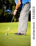 male golfer about to shot in a putting green near the hole - stock photo