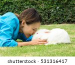 Stock photo asian beautiful woman kiss adorable new zealand white rabbit or cute bunny on green grass 531316417