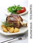 Small photo of pork shank with roasted potatoes, italian cuisine, stinco di maiale con patate arrosto