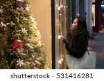 Small photo of An Asian girl stops in front of a window shop as her hair is blown by the wind, to admire a beautiful Christmas tree displayed under the warm lights in Edinburgh City center, Scotland, United Kingdom.