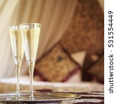 Small photo of Two champagne glasses with oriental canopy bed at the background. Silver tray. Romantic concept. Valentines background. Arabian nights ambiance. Square, glasses on left side, blur background