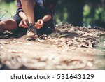 Young Woman Hiker Stops To Tie...