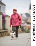 Senior Woman Walking Her Littl...