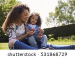 young mother sitting on grass... | Shutterstock . vector #531868729