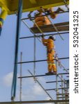 Small photo of Motion blur. Working at height. Scaffolders complete with falling protection doing scaffolding platform erection activities.