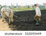 Small photo of Tyumen, Russia - June 24, 2016: The 5th open championship of Russia on plowed land. Draught horse pulles plough through field. Draught horse was traditionally used in ploughing before mechanisation