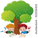 two boys reading book under tree