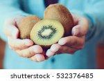 Holding Fresh Kiwi Fruit In...