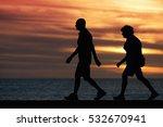 Small photo of Seniors walking brisk walk along the shore at sunset