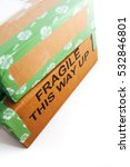 Small photo of A pile of 2 wrapped up parcels on a white background, with blank labels and green recycled parcel tape