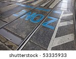 "road marking ""zone"" in vibrant blue letters on asphalt surface after some rain. - stock photo"