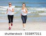 two women running on beach  | Shutterstock . vector #533897311