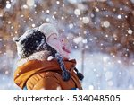 Small photo of Portrait of a cute little boy in warm clothes who catches snowflakes mouth in winter sunny day