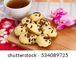 Small photo of Kue Cubit, Indonesian Cake, chocolate pancake Indonesian Version,served with cup of tea on wooden plate