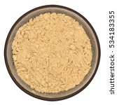 Small photo of Bio organic ginger powder in ceramic bowl isolated on white background, top view