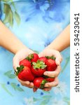 Woman offers freshly picked strawberries. Shallow DOF with selective focus on strawberries. - stock photo
