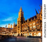 Small photo of Munich, Germany. Marienplatz at night with Town Hall of Munich, Germany and other buildings - cafes, bars, shops and restaurants. Reflection after the rain