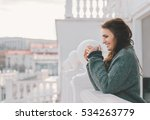 Small photo of Beautiful smiling woman relaxing and drinking coffee on the balcony in the morning