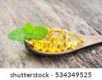 fish oil capsules on wood spoon.   Shutterstock . vector #534349525