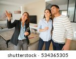 Small photo of Couple with real-estate agent visiting house for sale