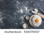 Small photo of The process of baking, cooking. Flour sprinkled on the gray table, rolling pin, whisk, egg shells sieve, spoon filled with flour. Pile the flour into a bowl with the egg yolk. Top view, space for text