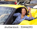 happy woman showing sitting inside of her new yewllo sports car - stock photo