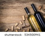 Small photo of Glass bottle of wine with corks on wooden table background